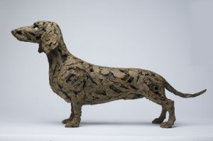 Bronze, textured sculpture of a dachshund by Joseph Paxton titled How to Win Friends and Influence People.