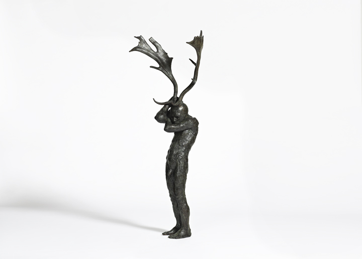 Bronze sculpture of a shy looking nude man with moose antlers sprouting from his head titled Antler Figure by Beth Carter.