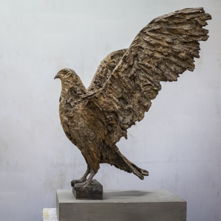 Bronze sculpture of a bird of prey standing upright with wings stretched behind itself by Joseph Paxton titled Bird of Prey.