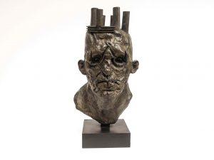 "Bronze sculpture of the weathered bust of an older man wearing a crown that looks more like industrial smokestacks protruding from his head by Beth Carter titled ""Hollow King."""