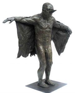 """Bronze sculpture of a man wearing a cone as a makeshift beak over his nose and holding up a torn cape as wings by Beth Carter titled """"Birdman (with Cloth Wings)."""""""